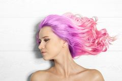 Portrait of young woman with dyed long curly hair. On white wooden background, top view. Trendy hairstyle design royalty free stock photo