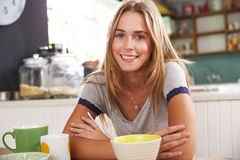 Portrait Of Young Woman Eating Breakfast In Kitchen Royalty Free Stock Photo