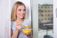 Portrait of young woman eating corn flakes at home Stock Photo