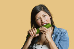 Portrait of a young woman eating cucumber over colored background Stock Photo