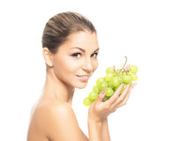 Portrait of a young woman eating fresh and tasty grapes Royalty Free Stock Photography