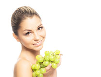 Portrait of a young woman eating fresh and tasty grapes Stock Photo
