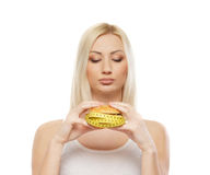 Portrait of a young woman eating a hamburger Stock Photo