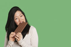 Portrait of a young woman eating a large chocolate bar over green background Royalty Free Stock Images