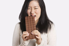 Portrait of a young woman eating a large chocolate bar over light gray background Stock Images