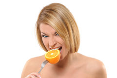 Portrait of a young woman eating an orange stock images