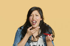 Portrait of a young woman eating red hot chili pepper over colored background Stock Photo