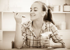 Portrait of young woman eating yoghurt at kitchen Stock Photo