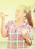 Portrait of young woman eating yoghurt at kitchen Royalty Free Stock Photography