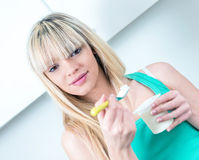 Portrait  young woman eating yogurt Royalty Free Stock Image