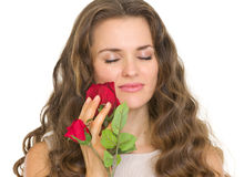 Portrait of young woman enjoying red rose Royalty Free Stock Image