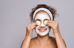 A portrait of a young woman with mask in a studio, beauty and skin care. A portrait of a young woman with face mask and cucumber in a studio, beauty and skin royalty free stock photo