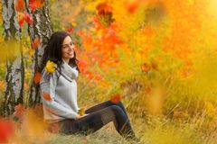 Portrait of young woman with falling autumn leaves. Royalty Free Stock Images
