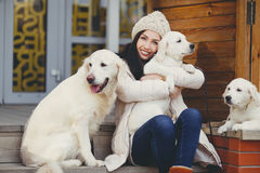 Portrait of the young woman with favourite dogs. The beautiful girl, the brunette with a long straight hair and gray eyes, in a white jacket and a beige knitted Stock Image