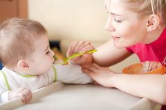 Portrait of young woman feeding her baby Stock Photo