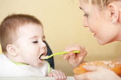 Portrait of young woman feeding her baby. Son Royalty Free Stock Photos
