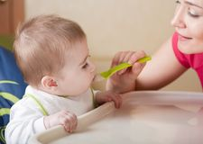 Portrait of young woman feeding her baby Royalty Free Stock Photography