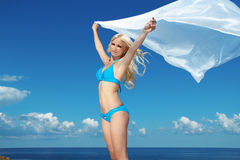 Portrait of young woman feeling free against blue sky with blowi. Ng fabric Royalty Free Stock Photography