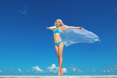Portrait of young woman feeling free against blue sky with blowi. Ng fabric. Freedom Concept Royalty Free Stock Image
