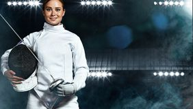 Young fencer athlete wearing fencing costume holding the sword and mask. On black background. Portrait of Young woman fencer wearing mask and white fencing royalty free stock photo