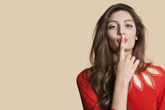 Portrait of a young woman with finger on lips over colored background Royalty Free Stock Photos