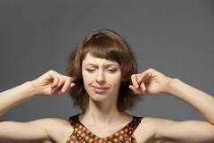 Portrait of young woman with fingers in ears Stock Photos