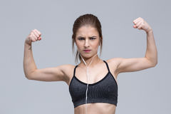 Portrait of young woman flexing her biceps Stock Images