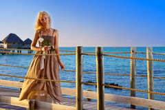 Portrait of the young woman with a flower against the sea during a sunset Stock Photo