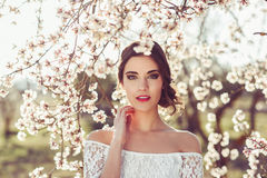 Portrait of young woman in the flowered garden in the spring tim Royalty Free Stock Photography