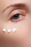 Portrait of young woman with fresh clean face with points of moisturizing cream under the eye Royalty Free Stock Image