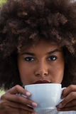 Portrait of young woman with frizzy hair holding coffee cup Royalty Free Stock Image