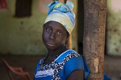 Portrait of a young woman in front of her home in the village of Mandina Mandinga in the Gabu Region. Gabu Region, Republic of Guinea-Bissau - February 7, 2018 royalty free stock image