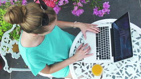 Portrait of a young woman in front of a laptop computer. Woman with laptop on vacation, outdoors. Woman using laptop computer on vacation in luxury resort. High stock video footage