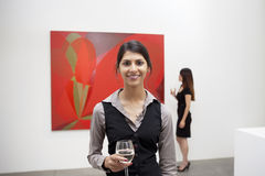 Portrait of young woman in front of painting in art gallery Stock Photography