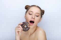 Portrait of a young woman with funny hairstyle and bare shoulders act the ape against white studio background with chocolate donut Royalty Free Stock Images