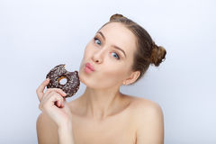 Portrait of a young woman with funny hairstyle and bare shoulders act the ape against white studio background with chocolate donut. Portrait of a young lady with Stock Image