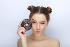 Portrait of a young woman with funny hairstyle and bare shoulders act the ape against white studio background with chocolate donut. Portrait of a young lady with Stock Photo