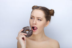 Portrait of a young woman with funny hairstyle and bare shoulders act the ape against white studio background with chocolate donut Royalty Free Stock Photography