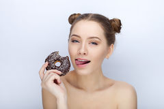 Portrait of a young woman with funny hairstyle and bare shoulders act the ape against white studio background with chocolate donut Stock Photo