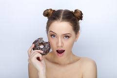 Portrait of a young woman with funny hairstyle and bare shoulders act the ape against white studio background with chocolate donut Royalty Free Stock Photo