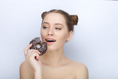 Portrait of a young woman with funny hairstyle and bare shoulders act the ape against white studio background with chocolate donut Stock Image