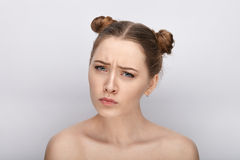Portrait of a young woman with funny hairstyle and bare shoulders act the ape against white studio background Stock Photo