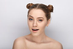 Portrait of a young woman with funny hairstyle and bare shoulders act the ape against white studio background Royalty Free Stock Photos
