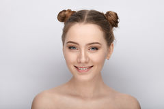 Portrait of a young woman with funny hairstyle and bare shoulders act the ape against white studio background Stock Image