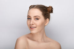 Portrait of a young woman with funny hairstyle and bare shoulders act the ape against white studio background Royalty Free Stock Photo