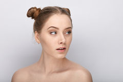Portrait of a young woman with funny hairstyle and bare shoulders act the ape against white studio background Stock Images