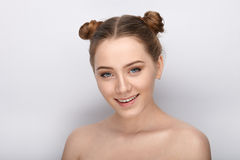 Portrait of a young woman with funny hairstyle and bare shoulders act the ape against white studio background Royalty Free Stock Photography