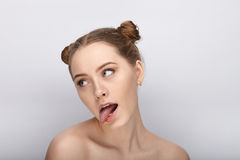 Portrait of a young woman with funny hairstyle and bare shoulders act the ape showing tongue against white studio background. Portrait of a young girl with funny royalty free stock photos