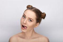 Portrait of a young woman with funny hairstyle and bare shoulders act the ape showing tongue against white studio background. Portrait of a young girl with funny royalty free stock photography