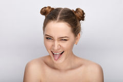 Portrait of a young woman with funny hairstyle and bare shoulders act the ape showing tongue against white studio background Royalty Free Stock Image